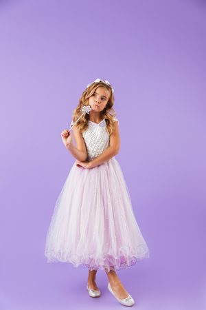 Full length portrait of a smiling pretty girl dressed in a princess dress isolated over violet background, holding magic wand