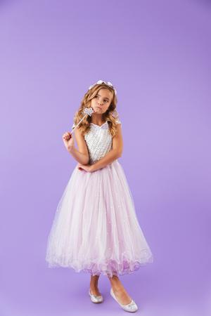 Retrato de cuerpo entero de una niña bonita sonriente vestida con un vestido de princesa aislado sobre fondo violeta, sosteniendo la varita mágica Foto de archivo