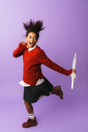 Full length of a cheerful african girl student posing with an umbrella isolated over violet background, jumping