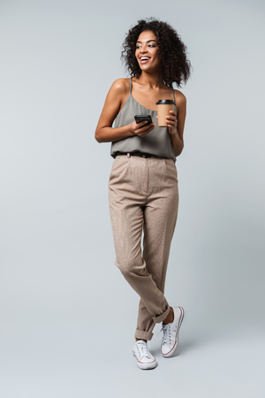 Full length of a happy young african woman casually dressed standing isolated over gray background,talking on mobile phone, holding takeaway cup of coffee Stock Photo