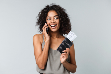 Smiling young african woman standing isolated over gray background, showing flight tickets with passport, talking on mobile phone Reklamní fotografie