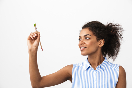 Beautiful young african woman atrist holding a paint brush over white background Archivio Fotografico - 116483780