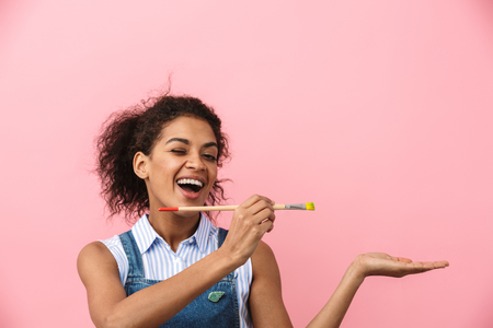 Beautiful young african woman atrist holding a paint brush over pink background, presenting copy space Archivio Fotografico - 116483763
