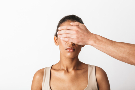 Scared young african woman sitting while mans hand covering her eyes isolated over white background
