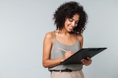 Gelukkig jonge Afrikaanse vrouw terloops gekleed permanent geïsoleerd over grijze achtergrond, het maken van aantekeningen in een notitieblok