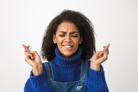Close up of a pretty worried young african woman wearing sweater standing isolated over white background, holding fingers crossed for good luck
