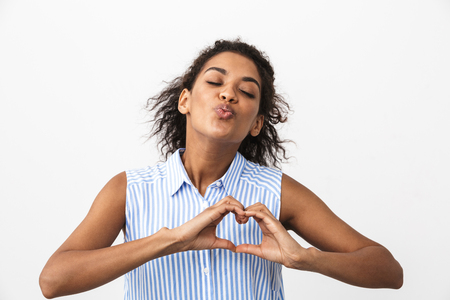 Beautiful young african woman standing over white background, showing love gesture Stockfoto