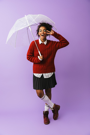 Full length of a cheerful african girl student posing with an umbrella isolated over violet background 스톡 콘텐츠
