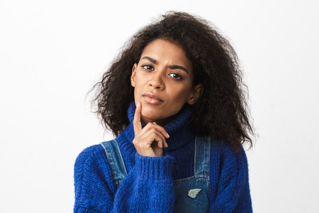 Close up of a pretty pensive young african woman wearing sweater standing isolated over white background Stock Photo