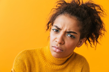 Upset young african woman wearing sweater standing isolated over yellow background