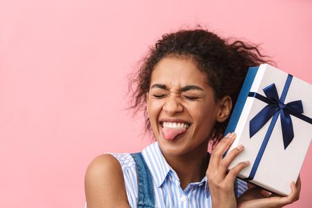 Hermosa mujer africana joven emocionada con caja de regalo sobre fondo de color rosa