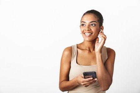 Beautiful young african woman casually dressed standing isolated over white background, wearing wireless earphones, using mobile phone
