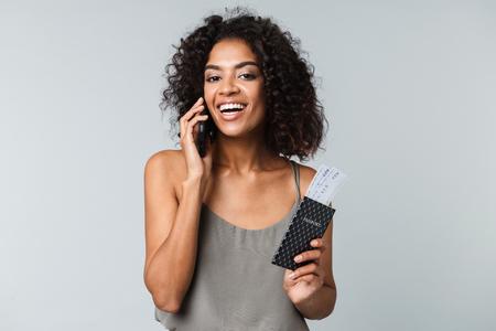 Glimlachende jonge afrikaanse vrouw die geïsoleerd staat over een grijze achtergrond, vliegtickets toont met paspoort, pratend op mobiele telefoon