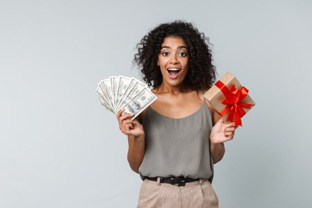 Happy young african woman casually dressed standing isolated over gray background, holding a gift box, showing money banknotes