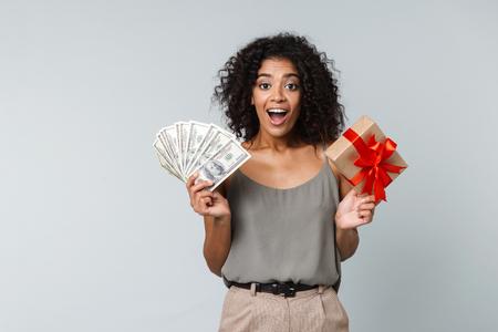愉快的年轻非洲妇女随便穿戴的站立被隔绝在灰色背景,拿着一个礼物盒,显示金钱钞票
