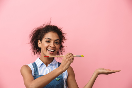 Beautiful young african woman atrist holding a paint brush over pink background, presenting copy space Archivio Fotografico - 116483566