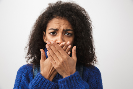 Close up of a pretty shocked african woman wearing sweater standing isolated over white background, cover mouth