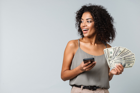 Happy young african woman standing isolated over gray background, holding bunch of money banknotes, using mobile phone