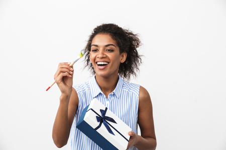 Beautiful young african woman standing over white background, holding gift box, showing paint brush Archivio Fotografico - 116483546