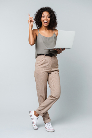 Full length of a happy young african woman casually dressed standing isolated over gray background, working on laptop computer, having an idea