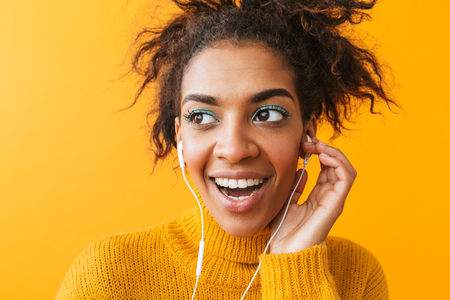 Cheerful african woman wearing sweater standing isolated over yellow background, listening to music with earphones