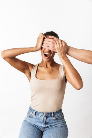 Scared screaming young african woman sitting while man's hand covering her eyes isolated over white background Archivio Fotografico - 116483529