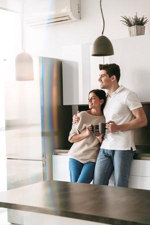 Glückliches schönes junges Paar, das Tassen hält, während es zu Hause in der Küche steht und auf das Fenster schaut