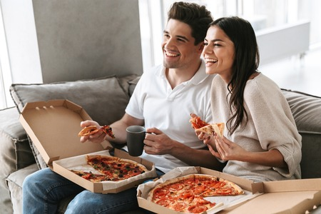 Cheerful young couple sitting on a couch at home, eating pizza, watching TV