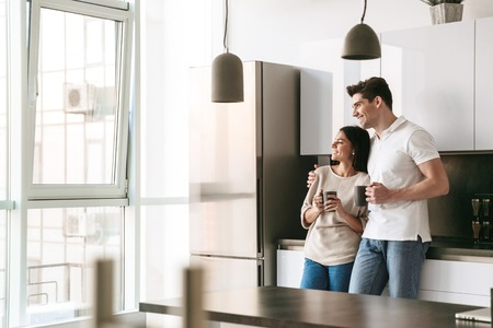 Happy lovely young couple holding cups while standing at the kitchen at home, looking at the window Imagens
