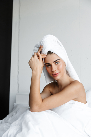 Beautiful young woman wrapped in bath towel sitting in bed