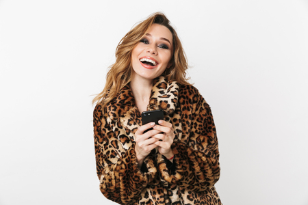 Beautiful cheerful young woman wearing leopard coat standing isolated over white background, holding mobile phone