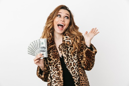 Beautiful young woman wearing leopard coat standing isolated over white background, showing money banknotes