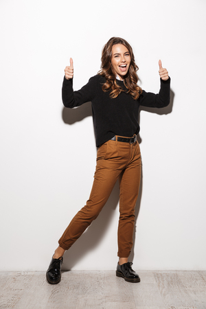 Full length of a cheerful young woman wearing sweater standing over white background, pointing fingers up at copy space Stock Photo - 116724678