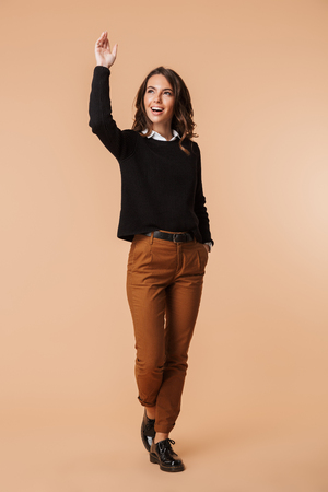 Full length of a cheerful young woman wearing sweater standing isolated over beige background, looking away