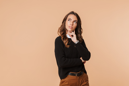 Image of european woman 20s thinking and touching chin with brooding glance isolated over beige background Banco de Imagens - 116725168