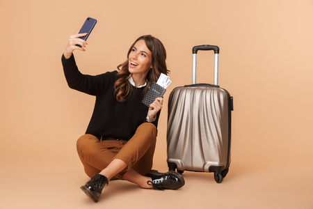 Young woman with baggage taking selfie photo on smartphone and holding travel ticket while sitting on floor isolated over beige background