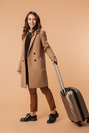 Full length of a smiling young woman wearing a coat standing with a travel bag isolated over beige background