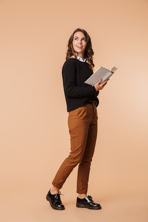 Full length of a cheerful young woman wearing sweater standing isolated over beige background, holding a book, looking up