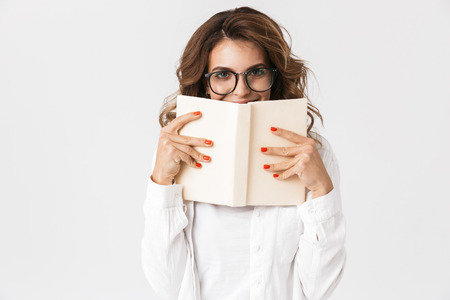 Portrait of brunette woman wearing eyeglasses reading book while standing isolated over white background Reklamní fotografie
