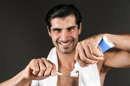 Smiling shirtless man with towel on his shoulders standing isolated over black background, putting toothpaste on a toothbrush