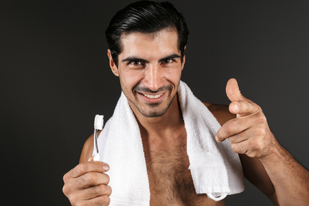 Smiling shirtless man with towel on his shoulders standing isolated over black background, holding toothbrush