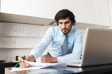 Image of a concentrated young business man at the kitchen wearing headphones work with documents using laptop computer. Stock Photo