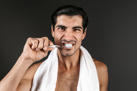 Smiling shirtless man with towel on his shoulders standing isolated over black background, brushing teeth