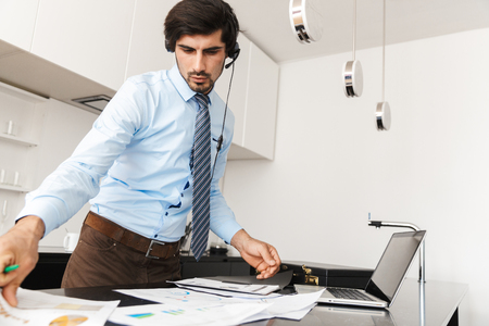 Image of a concentrated young business man at the kitchen wearing headphones work with documents. Stock Photo