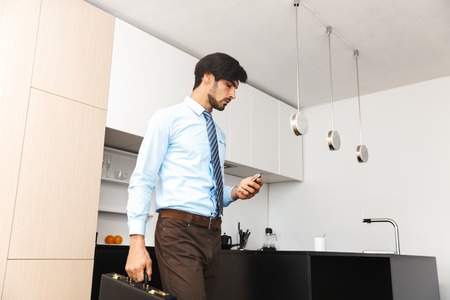 Image of a serious concentrated young business man at the kitchen holding suitcase using mobile phone. 스톡 콘텐츠