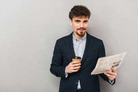 Photo of a handsome young business man isolated over grey wall background reading newspaper drinking coffee.