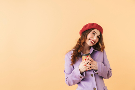 Portrait of shy woman 20s in coat and hat holding takeaway coffee while standing isolated over beige background