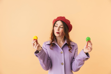 Image of caucasian woman 20s with long hair smiling and holding macaroon cookies standing isolated over beige background