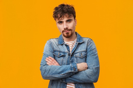 Handsome young bearded man standing isolated over orange, arms folded