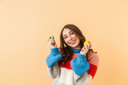 Image of pretty woman 20s with long hair smiling and holding macaroon cookies standing isolated over beige background